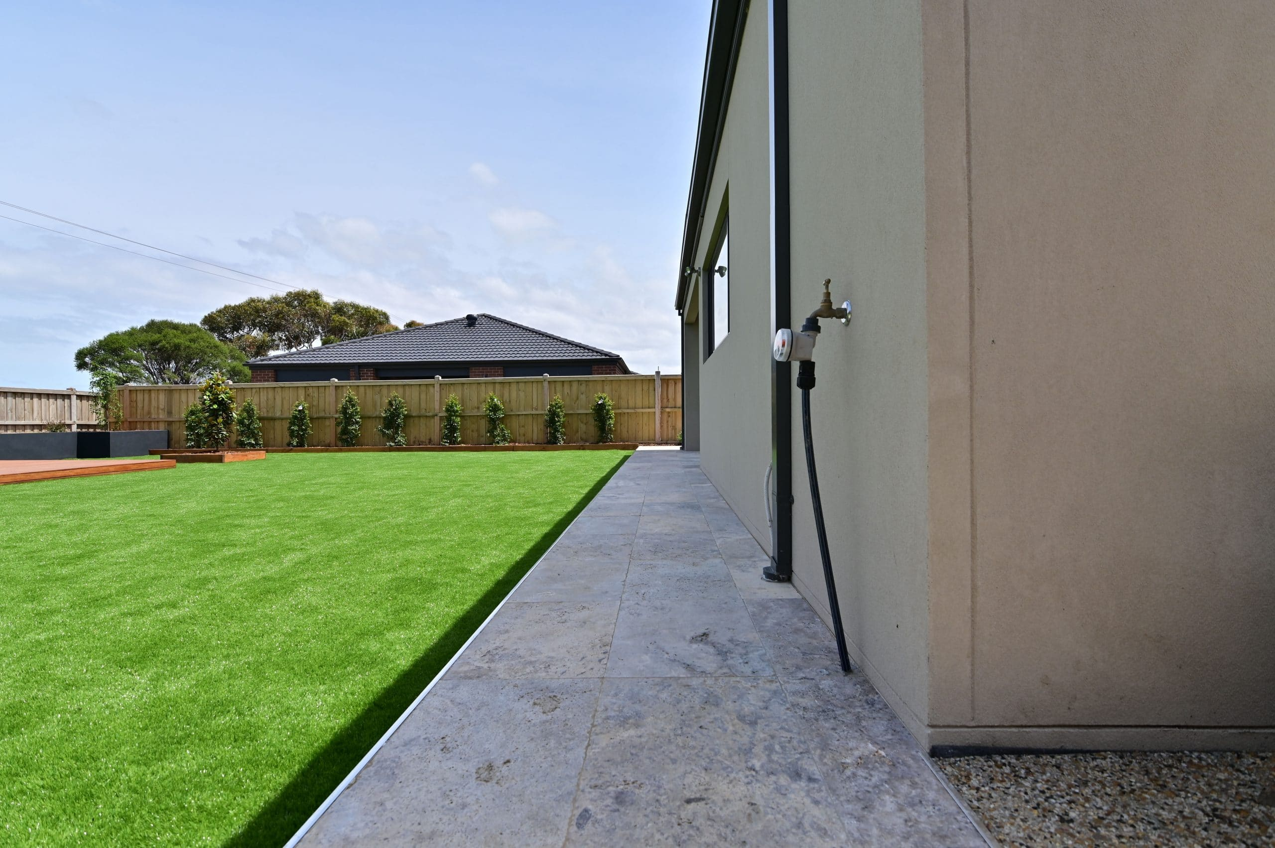 L266 - Point Cook - Backyard with grass, garden beds and a path